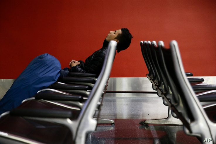 A man sleeps at the Los Angeles International Airport, Nov. 27, 2013, in Los Angeles. More than 43 million people are to travel over the long holiday weekend, according to AAA.