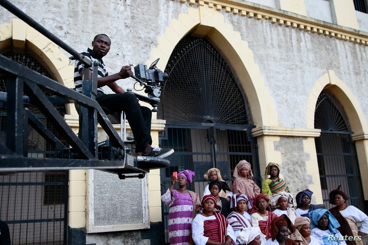 """FILE - A cameraman films a scene from a crane during the making of """"Ake,"""" a film based on the childhood memoirs of Nigerian writer Wole Soyinka, in Abeokuta, southwest Nigeria, July 14, 2013. Nigeria's movie business, often known as Nollywood, is one..."""