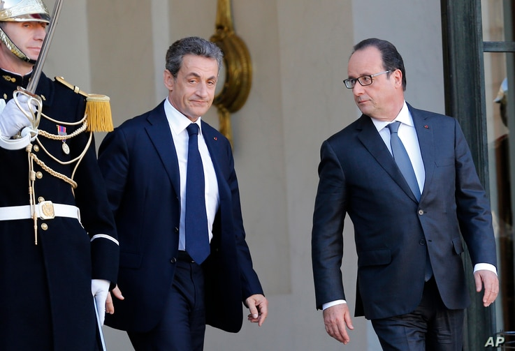 Former French President, Nicolas Sarkozy, leaves the Elysee Palace after a meeting with France's President, Francois Hollande, right,  in Paris, Sunday, Nov. 15, 2015.