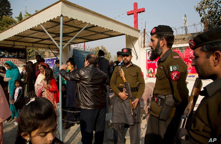 Pakistani paramilitary officers and policemen on alert as Pakistani Christians leave a church after attending the Christmas mass at a church in Islamabad, Pakistan, Dec. 25, 2016.