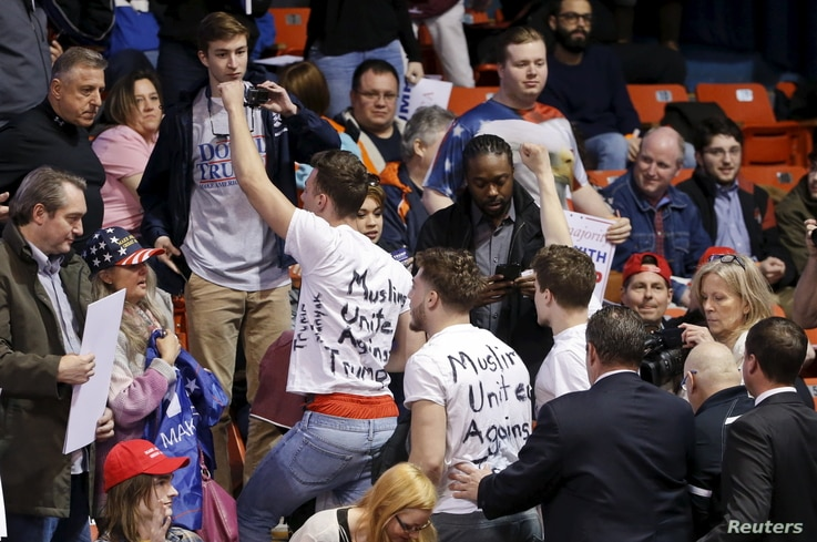 Protesters are escorted out of UIC Pavilion before Republican U.S. presidential candidate Donald Trump's rally at the University of Illinois at Chicago, March 11, 2016.