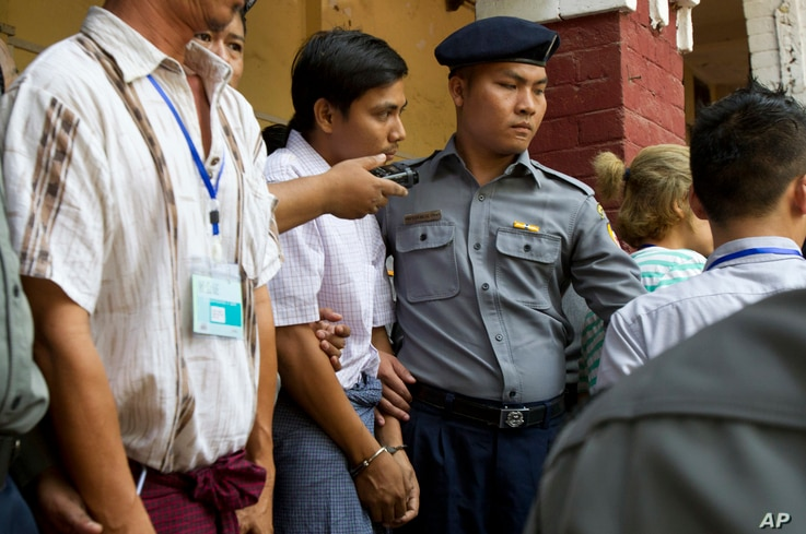 Reuters journalist Kyaw Soe Oo, center, is escorted by police as they leave the court,  April 4, 2018, Yangon, Myanmar.