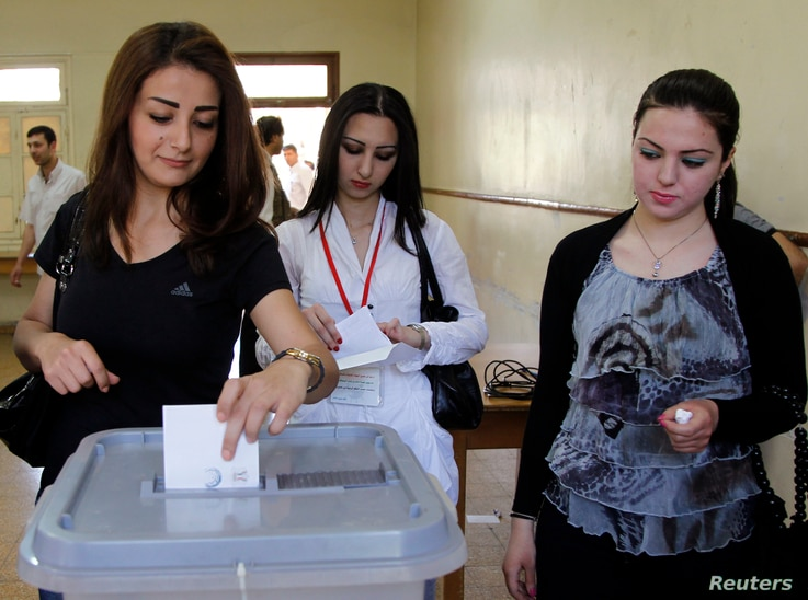 FILE - Women vote at a polling station for a parliamentary election, in Damascus, May 7, 2012.