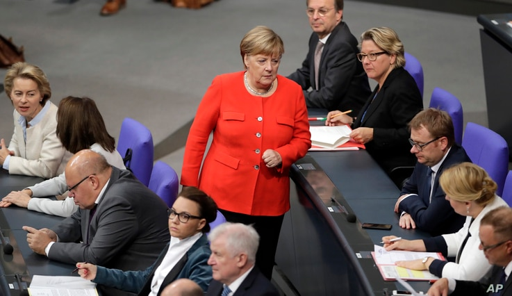 FILE - German Chancellor Angela Merkel, center, walks between ministers and state secretaries during a meeting of the German federal parliament, Bundestag, at the Reichstag building in Berlin, Germany, Sept. 27, 2018.