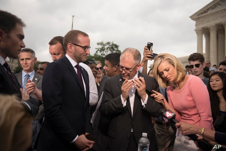 Jim Obergefell,  the named plaintiff in the case before the Supreme Court, center, talks on a cellphone to President Barack Obama on the steps of the Supreme Court following the court's decision, in Washington, D.C., June 26, 2015.