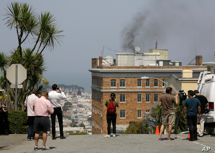 People stop to watch black smoke coming from the roof of the Consulate-General of Russia in San Francisco, Sept. 1, 2017.