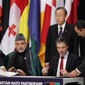 Afghan President Hamid Karzai and NATO Secretary General Anders Fogh Rasmussen sign a declaration between NATO and the Afghan government on enduring partnership, as UN General Secretary Ban ki-Moon, centre, looks on at the NATO summit in Lisbon (file...