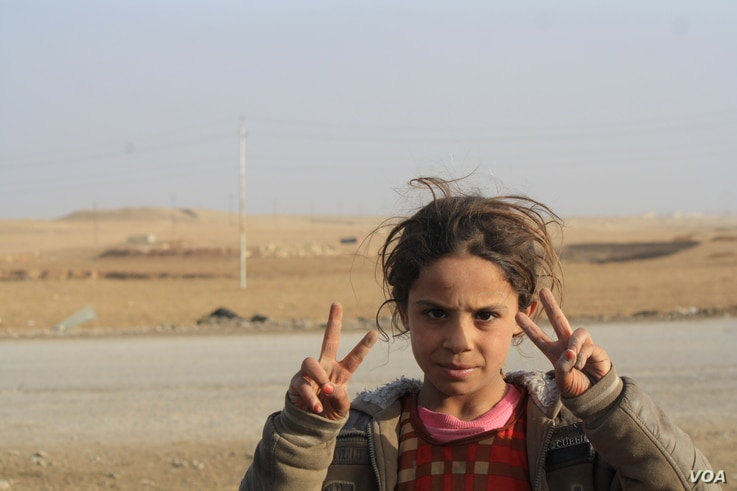 5019: Initially told by IS militants that Shia-led forces would attack them in a fit of violence, local children wave victory signs at passing Hashd Shaabi vehicles near Bashmana, Iraq, Dec. 16, 2016.
