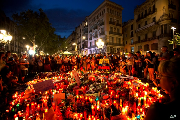 People gather at a memorial tribute of flowers, messages and candles to the victims on Barcelona's historic Las Ramblas promenade on the Joan Miro mosaic, embedded in the pavement where the van stopped after killing at least 13 people in Barcelona , ...