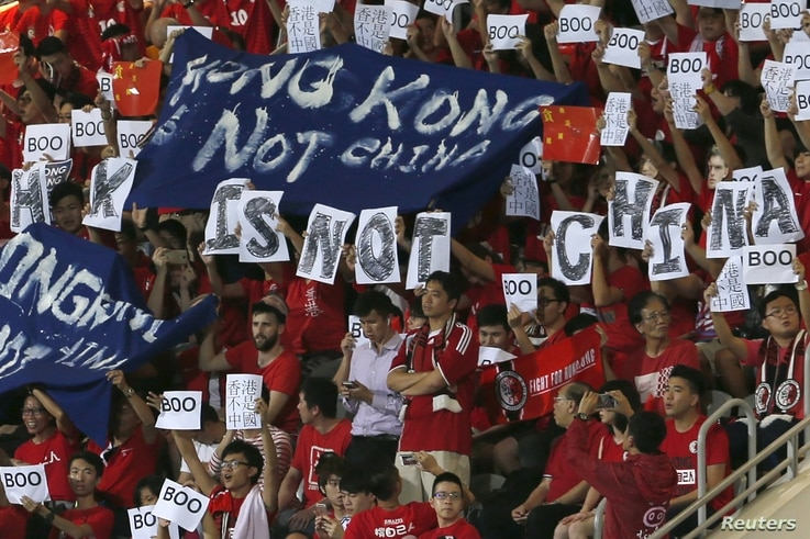 "Hong Kong fans hold banners and character signs that read ""Hong Kong is not China,"" during the Chinese national anthem at the 2018 World Cup qualifying match between Hong Kong and China, in Hong Kong, Nov. 17, 2015."