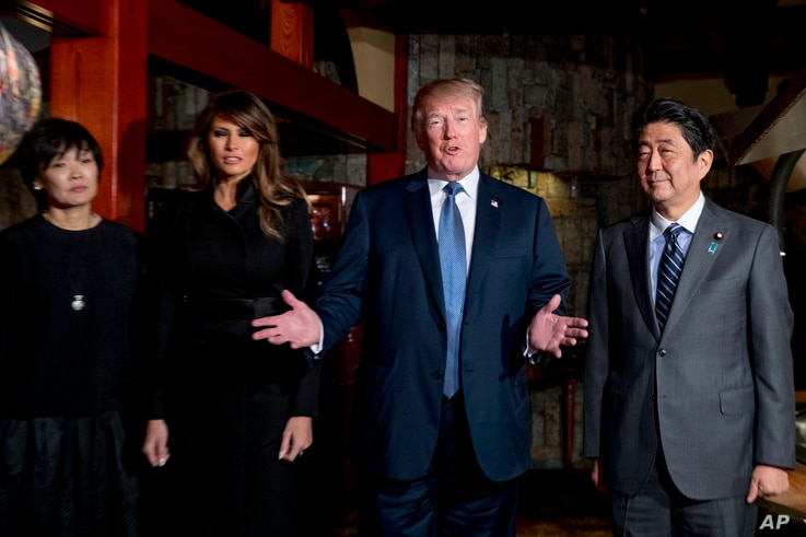 U.S. President Donald Trump, accompanied by first lady Melania Trump, second from left, Japanese Prime Minister Shinzo Abe and his wife Akie Abe, left, speaks to members of the media before having a dinner at Ginza Ukai Tei restaurant, Nov. 5, 2017, ...