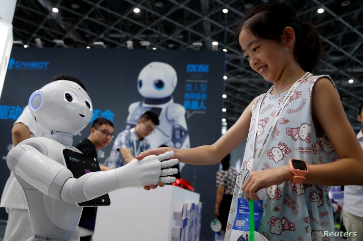 A visitor shakes hands with a humanoid robot at 2018 China International Robot Show in Shanghai, China, July 4, 2018.