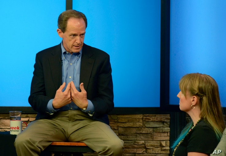Pennsylvania's U.S. Sen. Pat Toomey answers a question from Nancy Rohrbaugh, of Dillsburg, Pa., right, during an hourlong question-and-answer session in the studios of WHTM-TV, July 5, 2017 in Harrisburg, Pa. Toomey took questions in front of a live ...