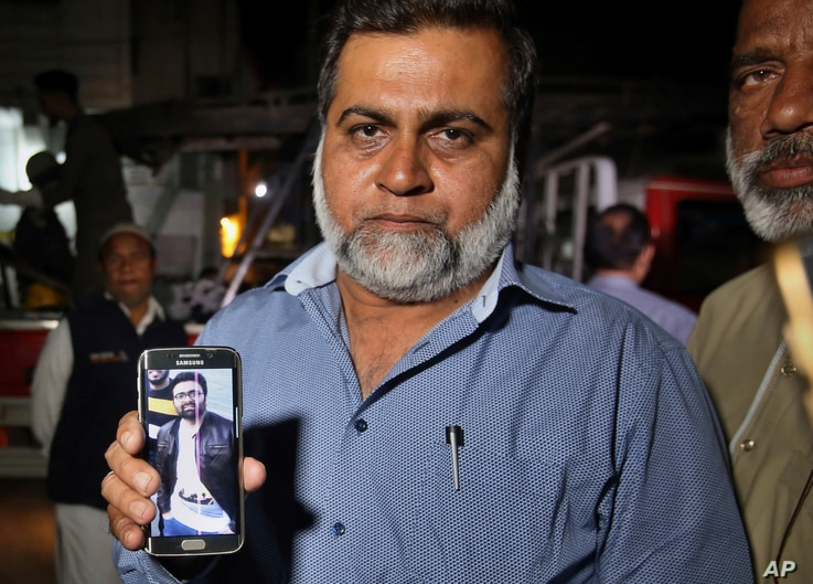 A relative shows a picture of Syed Areeb Ahmed, a Pakistani citizen who was killed the Christchurch mosque shootings, on his cellphone outside his home in Karachi, Pakistan, March 16, 2019. Pakistan's foreign minister says at least six Pakistanis wer...