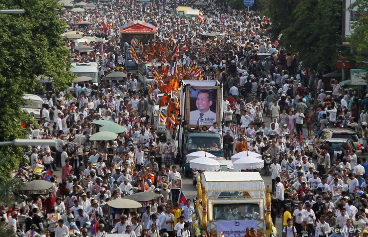 """Tens of thousands of people attend a funeral procession to carry the body of Kem Ley, an anti-government figure and the head of a grassroots advocacy group, """"Khmer for Khmer"""" who was shot dead on July 10, to his hometown, in Phnom Penh, Cambodia July"""