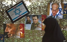 A woman walks past anti-Israel posters depicting Israel's President Shimon Peres, Defense Minister Ehud Barak and a caricature of Prime Minister Benjamin Netanyahu (L-R) as she visits a war exhibition held by Iran's revolutionary guard, at Baharestan...