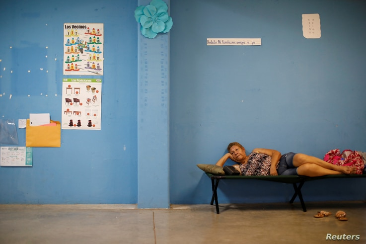 A woman rests in a school used as a shelter before the arrival of the Hurricane Maria in Guayama, Puerto Rico, Sept. 19, 2017.