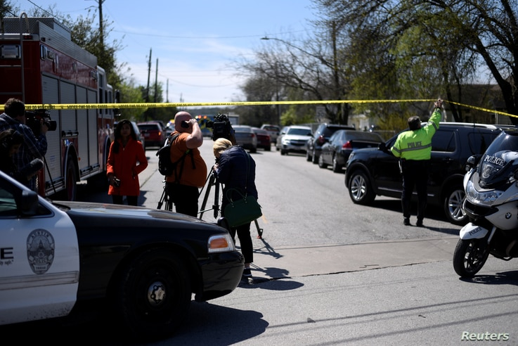 A police officer lifts crime scene tape to let in a car outside the scene of one of two bombings in Austin, Texas, March 12, 2018.