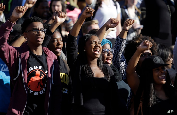 FILE - In this Nov. 9, 2015, photo, students cheer while listening to members of the black student protest group Concerned Student 1950.