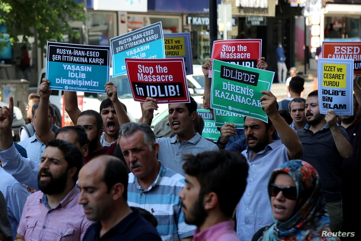 Demonstrators shout slogans during a protest against a Syrian military operation in the rebel-held Idlib province of northwest Syria, in Diyarbakir, Turkey. Sept. 7, 2018.