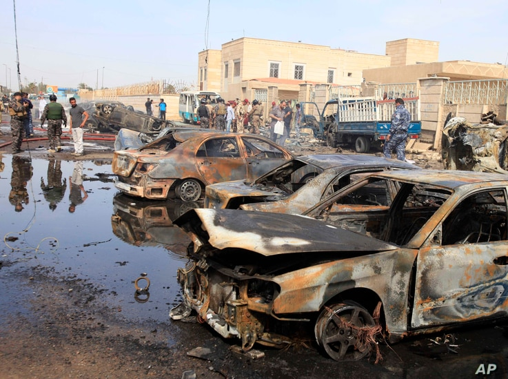 Civilians and security forces gather at the scene of a car bomb attack in Baghdad, Iraq, March 29, 2013.