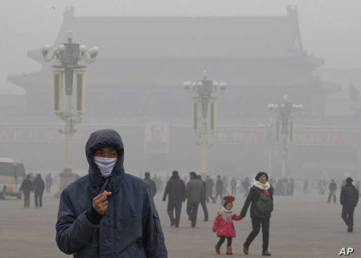 A man wears a mask on Tiananmen Square in thick haze in Beijing Tuesday, Jan. 29, 2013. Extremely high pollution levels shrouded eastern China for the second time in about two weeks.  (AP Photo/Ng Han Guan)