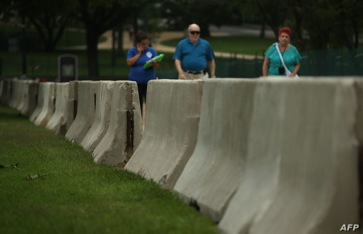 Barricades are seen as tourists pass by at the west front of the U.S. Capitol in Washington, D.C., where security has been increased for the upcoming July 4 holiday, July 2, 2015.