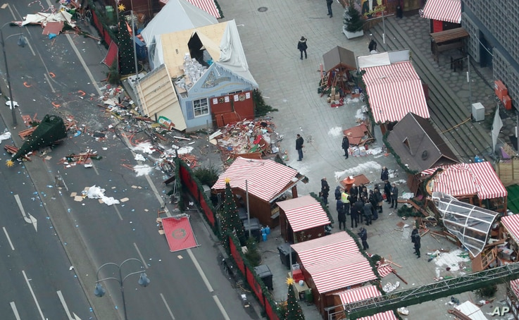 German Chancellor Angela Merkel and other government members visit the site of the attack in Berlin, Germany, Dec. 20, 2016, the day after a truck ran into a crowded Christmas market and killed several people.