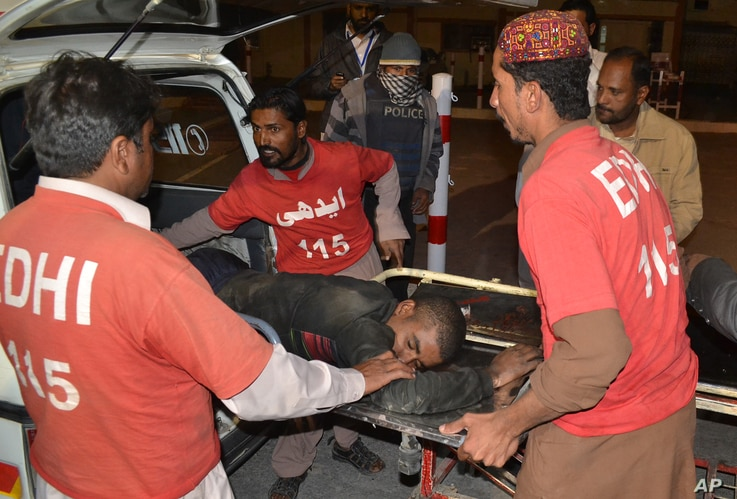 Pakistani volunteers rush an injured person to a hospital in Quetta, Pakistan, Oct. 24, 2016, after two separate attacks in Pakistan.  Gunmen stormed a police training center in the southwestern province of Baluchistan Monday, leaving several people...