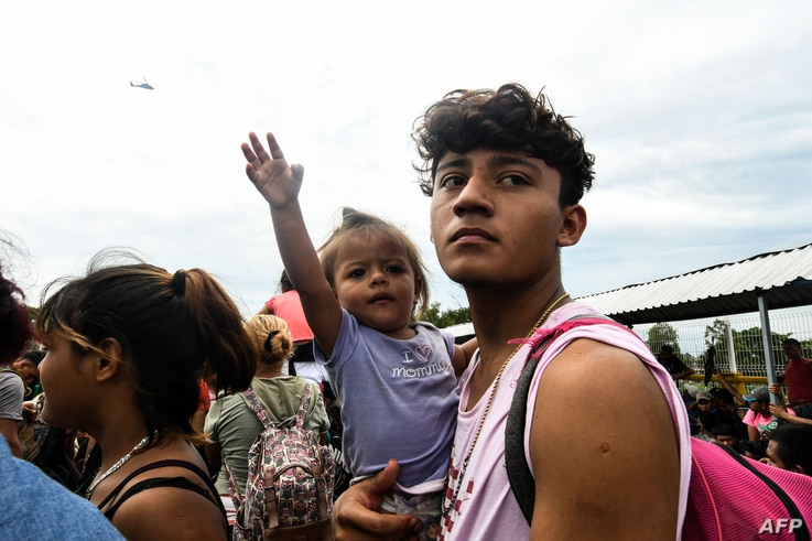 Honduran migrants taking part in a caravan heading to the US, arrive at the border crossing point with Mexico, in Ciudad Tecun Uman, Guatemala, on Oct. 19, 2018.