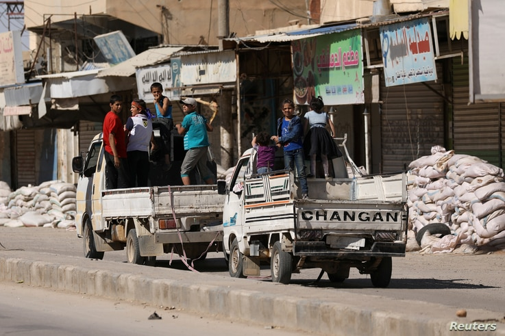 Vehicles carrying children drive past stacked sandbags in the town of Tabqa, after Syrian Democratic Forces (SDF) captured it from Islamic State militants this week, Syria May 12, 2017.