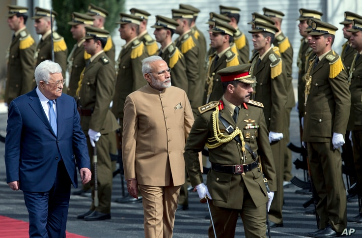 Palestinian President Mahmoud Abbas, left, and Indian Prime Minister Narendra Modi inspect an honor guard upon his arrival at Palestinian Authority headquarters in the West Bank city of Ramallah, Feb. 10, 2018.