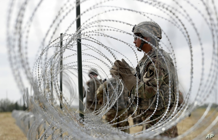 Members of a U.S Army engineering brigade place Concertina wire around an encampment for troops, Department of Defense and U.S. Customs and Border Protection near the U.S.-Mexico International bridge, Nov. 4, 2018, in Donna, Texas.