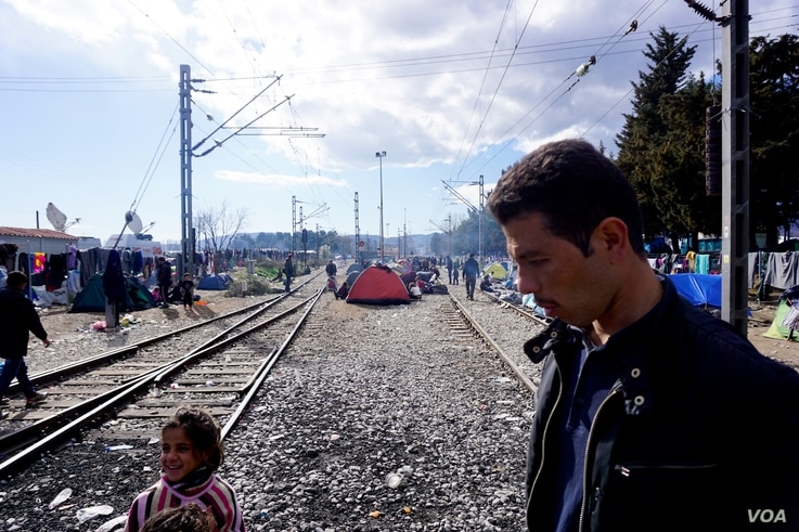 A man walks amid a makeshift encampment, with tents set up between train tracks in the northern Greek border town of Idomeni, March 4, 2016.