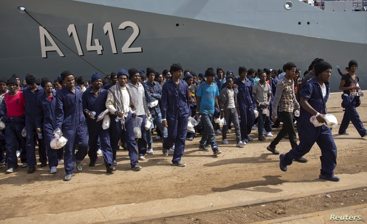 Migrants walk on the dock after disembarking from the German naval vessel Frankfurt Am Main in the Sicilian harbour of Augusta, Italy, April 12, 2016.