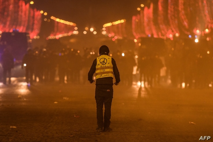 A protester wearing a Yellow Vest (Gilets jaunes) faces riot police during a demonstration of the 'Yellow Vests' (Gilets Jaunes)  against rising costs of living on the Champs Elysees avenue in Paris, Dec. 8, 2018.