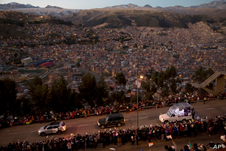 Pope Francis rides in his popemobile, right, as he greets people lining the road from El Alto to La Paz, upon his arrival to Bolivia, Wednesday, July 8, 2015.