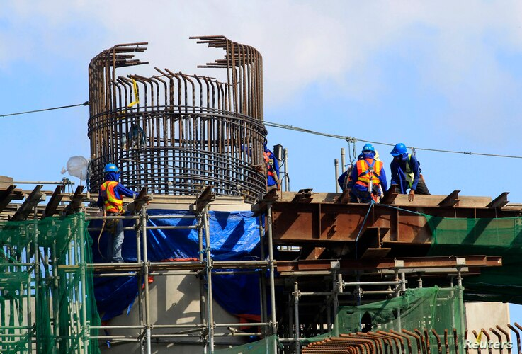 FILE - Workers balance on steel beams as they work on an expressway undergoing construction in Manila, Jan. 28, 2016. Growth in the Philippine economy picked up late in 2015 as strong domestic demand and government spending cushioned the impact of we...