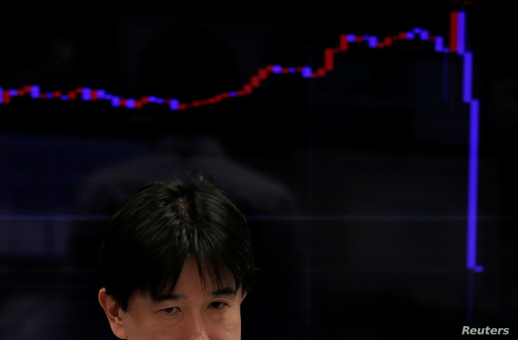An employee of a foreign exchange trading company works in front of a monitor displaying a graph of the Japanese yen's exchange rate against the U.S. dollar in Tokyo, Japan, Nov. 9, 2016.