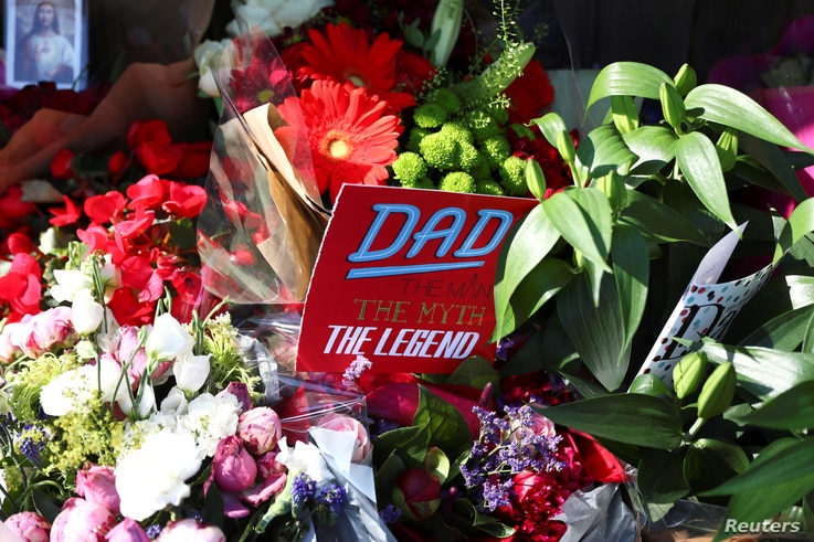 A father's day card sits amongst flowers left for the victims of the Grenfell apartment tower fire in North Kensington, London, Britain, June 18, 2017.