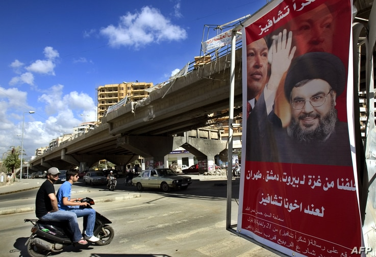 """FILE - A poster shows Hassan Nasrallah, the Secretary-General of Hezbollah, and Venezuela's President Hugo Chavez, along with a slogan that reads """"Gracias Chavez"""" is seen hanging from a destroyed bridge at the entrance of southern suburb of Beirut, S..."""