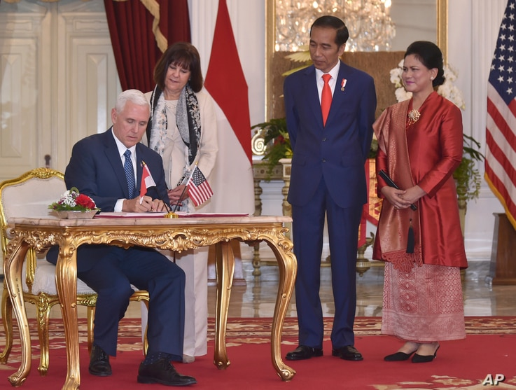 U.S. Vice President Mike Pence (left) with his wife, Karen, (second from left) signs the guest book as Indonesian President Joko Widodo and his wife, Iriana, look on, during their meeting at Merdeka Palace in Jakarta, Indonesia, April 20, 2017.