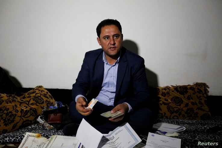 Botan Mahmoud Hassour shows his identity cards when he was working with the U.S. military as he awaits his date of travel to the U.S. as a refugee after U.S. President Donald Trump's decision to temporarily bar travelers from seven countries, includi...