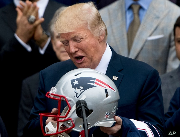 President Donald Trump is presented with a New England Patriots football helmet and jersey by Patriots coach Bill Belichick and  Patriots owner Robert Kraft during a ceremony on the South Lawn of the White House in Washington, April 19, 2017.
