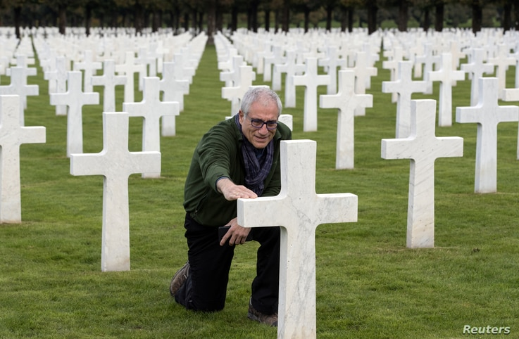 Jeffrey Gusky, a U.S. explorer and WWI enthusiast, touches the tombstone of fallen U.S. soldier Burton Holmes of the First World War's 371st infantry regiment, an African American unit, at the Meuse-Argonne American Cemetery and Memorial in Romagne...