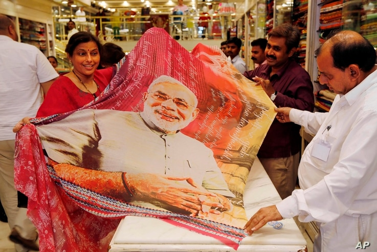 A woman customer holds a sari printed with a portrait of Bharatiya Janata Party's prime ministerial candidate Narendra Modi at a garments shop in Mumbai, May 14, 2014.