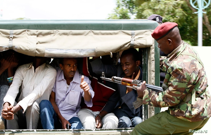 A policeman guards suspected Somali illegal migrants arrested at a holding station in Kenya's capital Nairobi, April 7, 2014.
