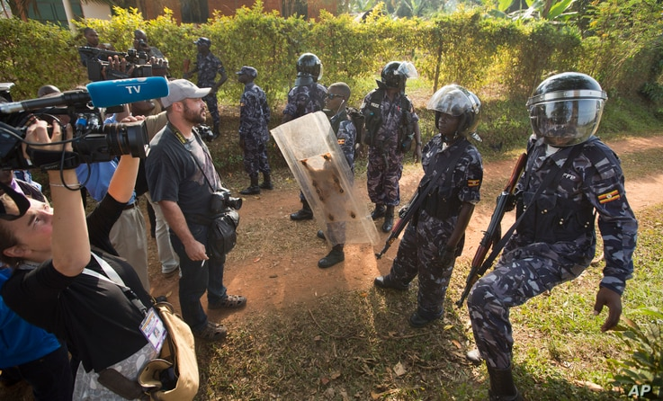 A line of riot police prevent the media from approaching Uganda's main opposition leader Kizza Besigye as he tries to leave his house in Kasangati, Uganda, Feb. 22, 2016.