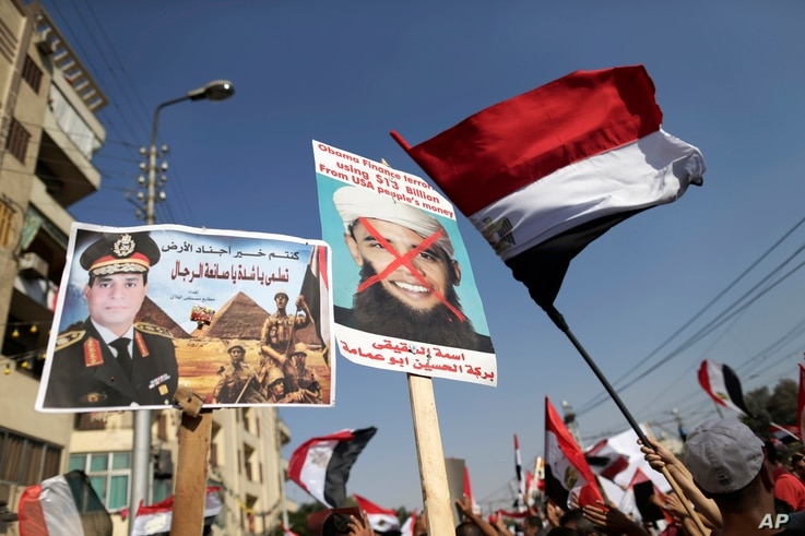 FILE - In this July 26, 2013, photo opponents of Egypt's ousted President Mohammed Morsi wave Egyptian flags and hold a poster depicting then general, Abdel-Fattah el-Sissi, while another holds an modified image of then President Barack Obama, showin...