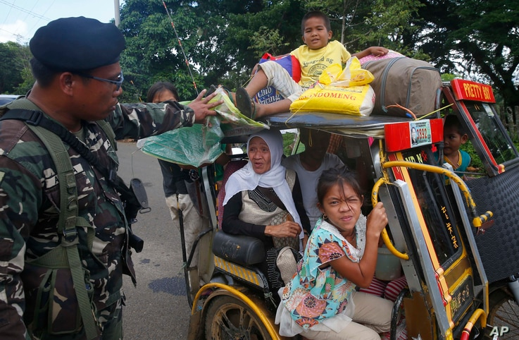 Residents fleeing the besieged city of Marawi are questioned at a checkpoint by government soldiers, May 26, 2017.
